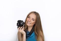 Headshot młoda urocza figlarnie blondynki kobieta z ślicznym uśmiechem w kobaltu koloru bluzce pozuje z czarną dslr kamerą na bie Fotografia Royalty Free