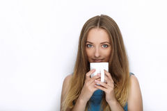 Headshot młoda urocza figlarnie blondynki kobieta z ślicznym uśmiechem w kobaltu koloru bluzce pozuje z dużym czystym białym kubk Obrazy Stock