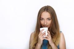 Headshot młoda urocza figlarnie blondynki kobieta z ślicznym uśmiechem w kobaltu koloru bluzce pozuje z dużym czystym białym kubk Obraz Royalty Free
