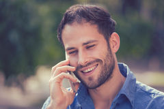 Headshot of a man talking on mobile phone outdoors. Headshot of a man talking on mobile phone. Casual urban professional using smartphone smiling happy standing royalty free stock photo
