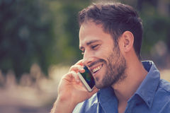 Headshot of a man talking on mobile phone outdoors. Headshot of a man talking on mobile phone. Casual urban professional using smartphone smiling happy standing Stock Image