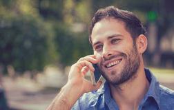 Headshot of a man talking on mobile phone outdoors. Headshot of a man talking on mobile phone. Casual urban professional using smartphone smiling happy standing stock images