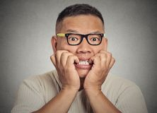 Headshot nerdy guy with glasses biting his nails looking anxious craving Stock Photography