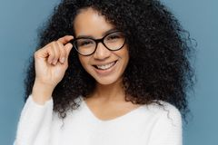 Headshot of optimisitc young African American woman with crisp hair, holds hand on frame of glasses, wears white sweater, being in stock images
