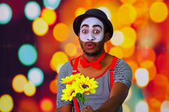 Headshot pantomime man with facial paint posing for camera holding sunflowers in hands, blurry lights background.  Royalty Free Stock Images