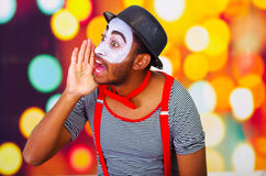 Headshot pantomime man with facial paint posing for camera using hands around mouth yelling, blurry lights background.  Stock Image
