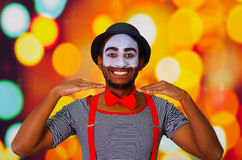 Headshot pantomime man with facial paint posing for camera using hands interacting, blurry lights background.  Royalty Free Stock Photos