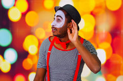 Headshot pantomime man with facial paint posing for camera using hands interacting, blurry lights background.  Stock Image