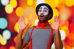 Headshot pantomime man with facial paint posing for camera using hands interacting, blurry lights background.  Royalty Free Stock Image