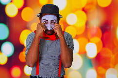 Headshot pantomime man with facial paint posing for camera using hands interacting rubbing eyes, blurry lights. Background Stock Photo