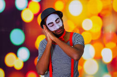 Headshot pantomime man with facial paint posing for camera using hands interacting sleeping, blurry lights background.  Royalty Free Stock Images