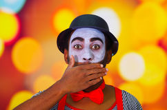 Headshot pantomime man with facial paint posing for camera using hands to cover mouth, blurry lights background.  Stock Images