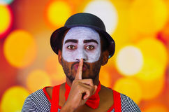 Headshot pantomime man with facial paint posing for camera using hands to cover mouth, blurry lights background.  Royalty Free Stock Photo