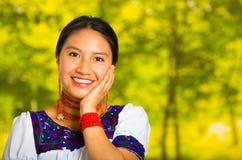 Headshot piękna młoda kobieta jest ubranym tradycyjną andyjską bluzkę z czerwoną kolią, pozuje dla kamery macania twarzy Zdjęcia Royalty Free