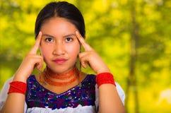 Headshot piękna młoda kobieta jest ubranym tradycyjną andyjską bluzkę z czerwoną kolią, pozuje dla kamery macania twarzy Zdjęcia Stock