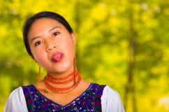 Headshot piękna młoda kobieta jest ubranym tradycyjną andyjską bluzkę z czerwoną kolią, pozuje dla kamery mienia jęzoru out Zdjęcia Stock