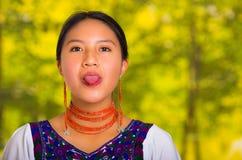 Headshot piękna młoda kobieta jest ubranym tradycyjną andyjską bluzkę z czerwoną kolią, pozuje dla kamery mienia jęzoru out Obrazy Stock