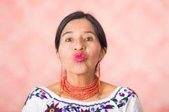Headshot pięknego latynosa macierzysta jest ubranym tradycyjna andyjska odzież, robi całowanie wargom kamera, różowy studio Zdjęcia Royalty Free