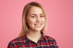 Headshot of pleasant looking blonde young European woman with toothy smile, minimal make up, wears checkered shirt, enjoys good. Atmosphere, being in high stock image