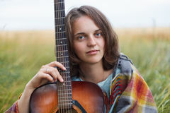 Headshot of pleasant-looking female with blue charming eyes and dark short hair sitting with guitar at green field looking directl Royalty Free Stock Image