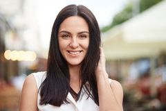 Headshot of pleased brunette female looks happily at camera, poses outdoor, enjoys spare time, models in open air against blurred royalty free stock photography