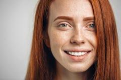 Headshot-Porträt des glücklichen Ingwermädchens mit Sommersprossen lächelnd, Kamera betrachtend Lizenzfreie Stockfotos