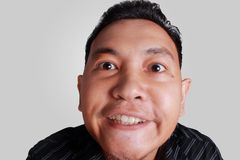 Cynical Asian Man Expression. Headshot portrait of funny Asian man showing cynical unhappy angry facial expression, isolated on grey Stock Image
