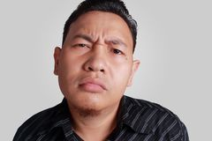 Cynical Asian Man Expression. Headshot portrait of funny Asian man showing cynical unhappy angry facial expression, isolated on grey Stock Photo