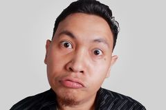 Cynical Asian Man Expression. Headshot portrait of funny Asian man showing cynical unhappy angry facial expression, isolated on grey Royalty Free Stock Image