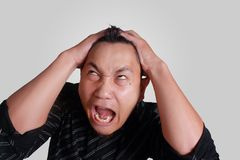 Asian Man Mad Angry Stressed Expression. Headshot portrait of funny young Asian man angry stressed furious expression, isolated on grey Royalty Free Stock Photo