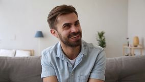 Headshot portrait guy sitting on couch talking looking at camera