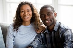 Portrait of happy mixed race couple posing for picture. Headshot portrait of happy young mixed race husband and wife sit on couch posing for family picture stock photography