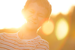 Headshot portrait of screwing up eyes laughing teenage boy in warm sunset backlit with lens flares Stock Photos