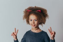 Headshot Portrait Sweet little girl   with curly hair  smiling looking at camera. gray background royalty free stock image
