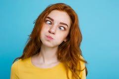 Headshot portret szczęśliwa imbirowa czerwona włosiana dziewczyna patrzeje kamerę z śmieszną twarzą Pastelowy błękitny tło kosmos zdjęcia royalty free