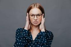 Headshot poważny żeński nauczyciel utrzymuje ręki na głowie, jaźń ufnego wyraz twarzy, jest ubranym widowiska, polki kropki biel zdjęcie stock