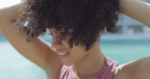 Wonderful young black woman with short curls. Headshot of pretty black girl with short curls and in casual outfit looking sensually at camera on city riverbank stock video