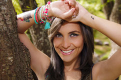 Headshot pretty brunette, standing between trees, bare skinned arms above head pose, sensually looking into camera Stock Photography