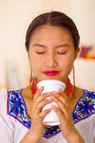 Headshot pretty young woman wearing traditional andean blouse, drinking coffee from white mug Royalty Free Stock Image