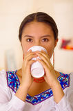 Headshot pretty young woman wearing traditional andean blouse, drinking coffee from white mug Stock Photos