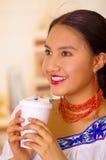 Headshot pretty young woman wearing traditional andean blouse, holding white coffee mug, enjoying a break Stock Image