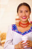 Headshot pretty young woman wearing traditional andean blouse, holding white coffee mug, facing camera, beautiful smile.  Royalty Free Stock Photo