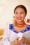 Headshot pretty young woman wearing traditional andean blouse, holding white coffee mug, facing camera, beautiful smile Royalty Free Stock Images
