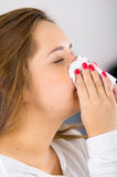 Headshot profile brunette sick with the flu blowing her nose Stock Photography