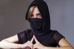 Headshot samurai woman dressed in black with matching veil covering face, resting arms on desk and touching fingertips. Against each other, facing camera, ninja Royalty Free Stock Images