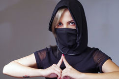 Headshot samurai woman dressed in black with matching veil covering face, resting arms on desk and touching fingertips Royalty Free Stock Photography