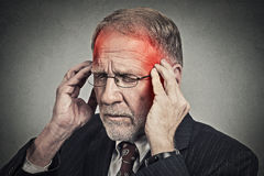 Headshot senior man suffering from headache hands on head Stock Images
