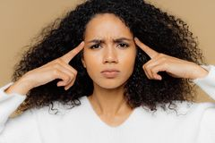 Headshot of stressful Afro American woman keeps index fingers on temples, suffers from headache frowns face, has dissatisfied stock image