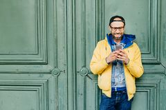Headshot of stylish man with beard and broad forehead in yellow anorak, jeans and cap in big glasses holding cell phone checking n. Ewsfeed on social network royalty free stock image