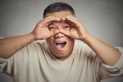 Headshot surprised curious guy, funny man, looking through binoculars Stock Photography